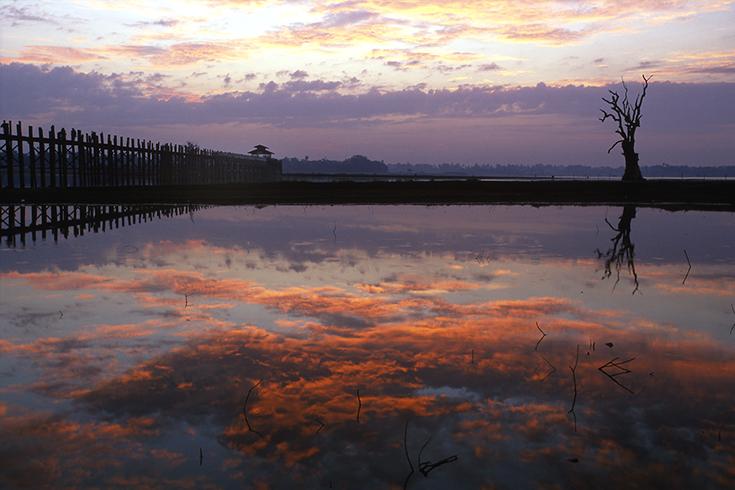 Tagesanbruch an der alten U Bein-Brücke nahe Amarapura. Seitdem der Taungthaman-See aufgestaut ist, spiegeln sich die Wolken in ihm das ganze Jahr über.