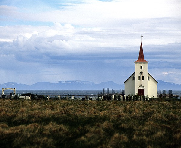 """Die Kirche von Kollafjarðarnes: Irgendwie erinnert mich diese Landschaft an Hernandez, New Mexico, das Ansel Adams 1941 in seiner berühmten Aufnahme """"Moonrise"""" abgelichtet hat. Es liegt wohl an der Graslandschaft mit den weißen Kreuzen."""