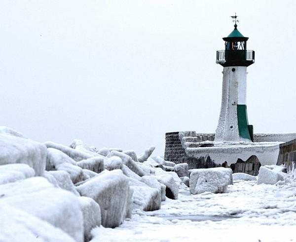 Der Leuchtturm von Sassnitz während eines strengen Winters. Die Wellenbrecher tragen dicke Eispanzer.